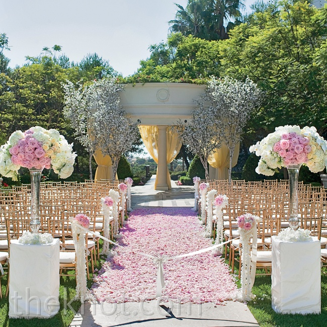 The ceremony took place on the resort's Pacific Lawn. At the end of the aisle carpeted with blush rose petals, staggered white cherry blossom trees marked the spot where the couple exchanged vows.