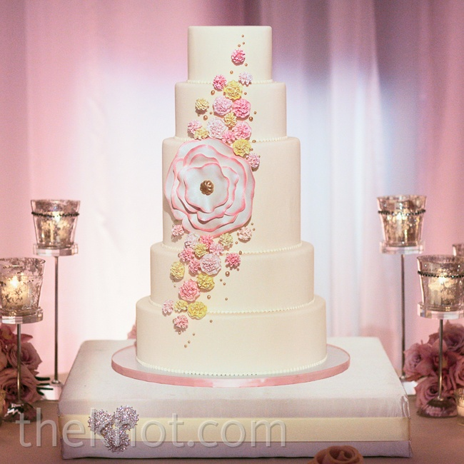 Multicolored sugar flowers cascaded down the glittery, five-tiered confection
