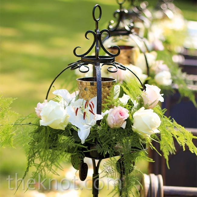 Candlelit stands, overflowing with pink and white flowers, were a romantic addition to the ceremony aisle.