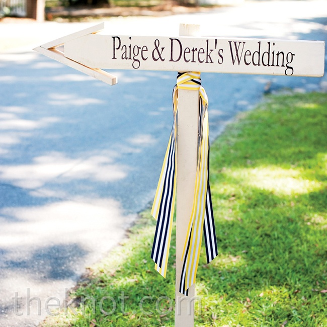 A wooden sign with blue-and-yellow-and-white-striped ribbon led the way to the ceremony.