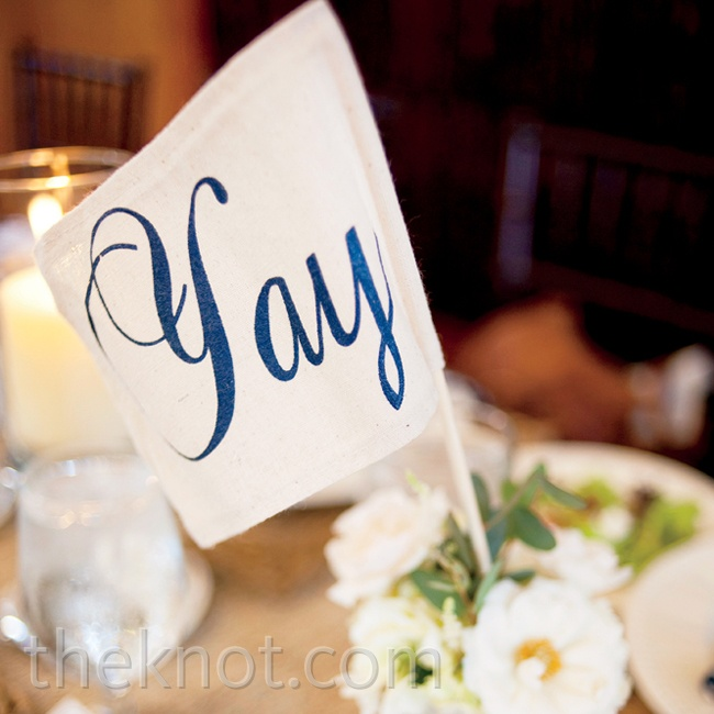 """Yay"" flags that guests waved during the ceremony later added a fun touch to the reception tables."