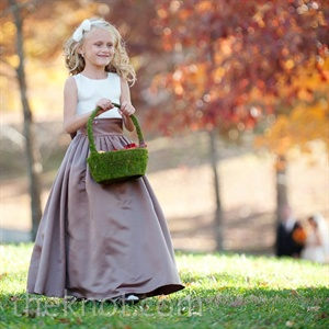 Carrying a moss-covered wicker basket, the couple's flower girl sprinkled the aisle with vibrant red, orange, and yellow petals.