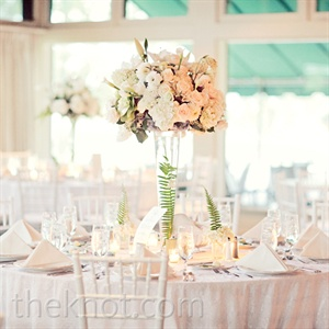 A mix of high and low white-and-green arrangements set atop white linens created a clean, modern look.