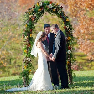 Elyse and Kyle exchanged vows standing before a grapevine arbor covered in fall-colored blooms.