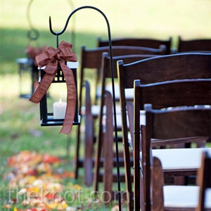 Dimly lit lanterns, each adorned with a chocolate satin bow, hung from shepherd's hooks.