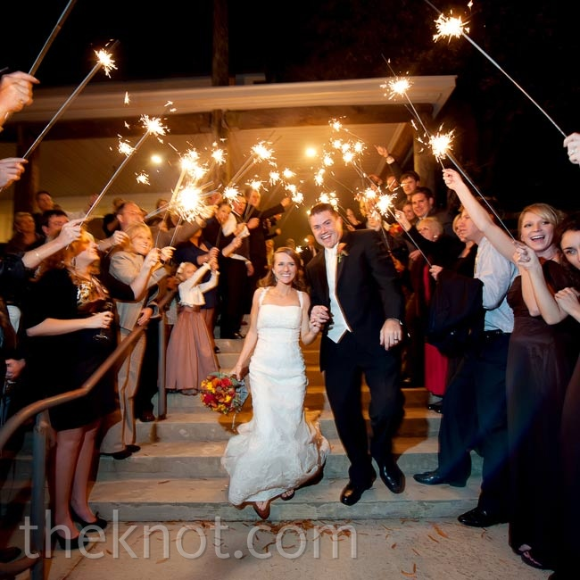 Standing on either side of the exit, guests waved sparklers as the couple made their way to a limousine.