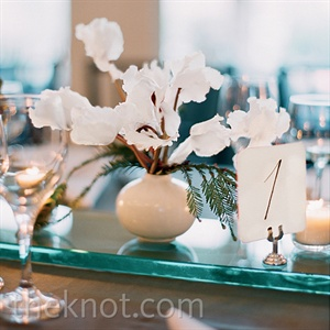 Handmade vases filled with white cyclamen (Kathryn's favorite winter flower) and evergreen accents topped the tables.