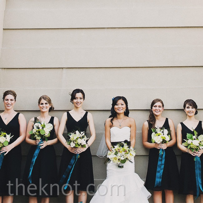 Aqua-hued sashes on the bouquets gave the simple black bridesmaid dresses a colorful boost.