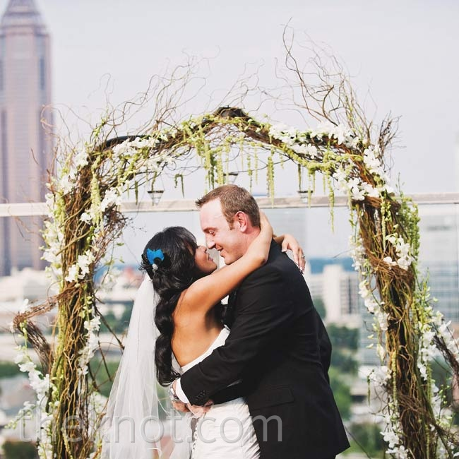 A romantic arch, covered in white blooms and greenery, was an earthy surprise to the couple's urban-set nuptials.