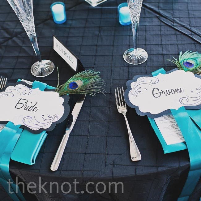 Teal napkins and fancy peacock feathers spruced up the couple's place settings.