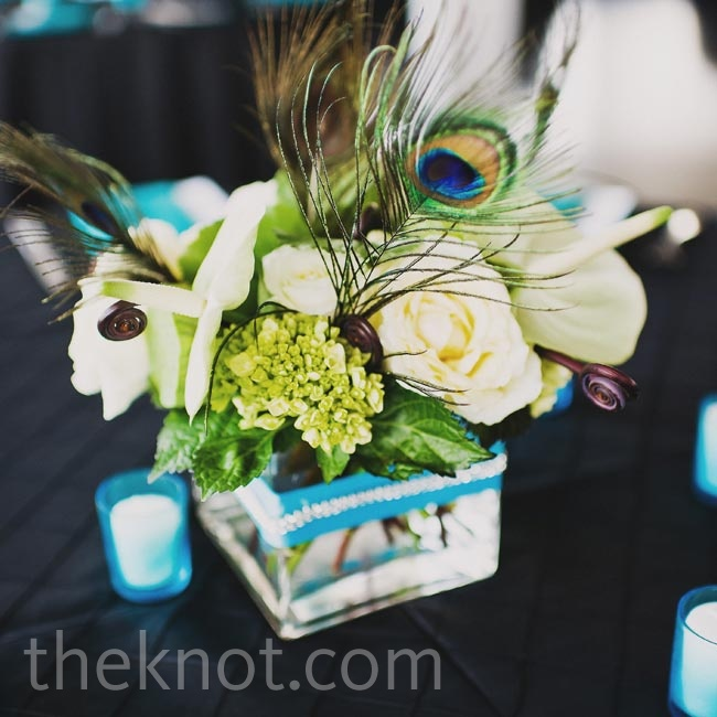 More peacock feathers were found in the centerpieces, which also included roses, hydrangeas, and button mums in square glass vases.