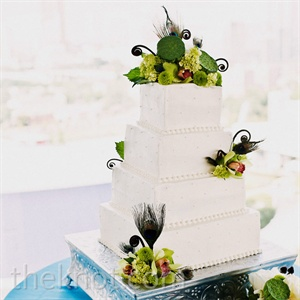 The all-white cake was coated in buttercream frosting and decorated with fresh flowers, lotus pods, and peacock feathers.