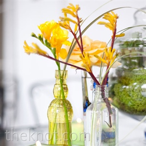 Glass bottles and apothecary jars, filled with bright single-stem flowers livened up the tabletops.
