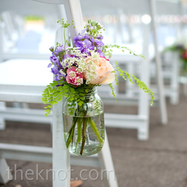 The ceremony aisles were lined with mason jars filled with pastel-hued blooms.