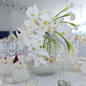White orchids, tulips and mini calla lilies in clear, crystal-filled glass vases were grouped with glass votives of various heights for an elegant yet modern look.