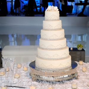 Swarovski-like bands and wave-like crystal detailing covered the white-fondant tiers; sugar orchids decorated the top.