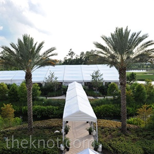 Palm trees surrounded the white reception tent, which was separated into two areas: one for tables and chairs, and one for the cake and dance floor.