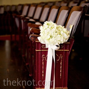The couple kept their ceremony space simple, and lined the aisles with bunches of ivory hydrangeas tied with satin ribbon.