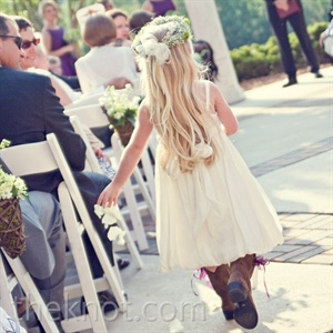 Wearing a sundress and cowboy boots, the couple's flower girl carried a wicker basket filled with ivory petals.
