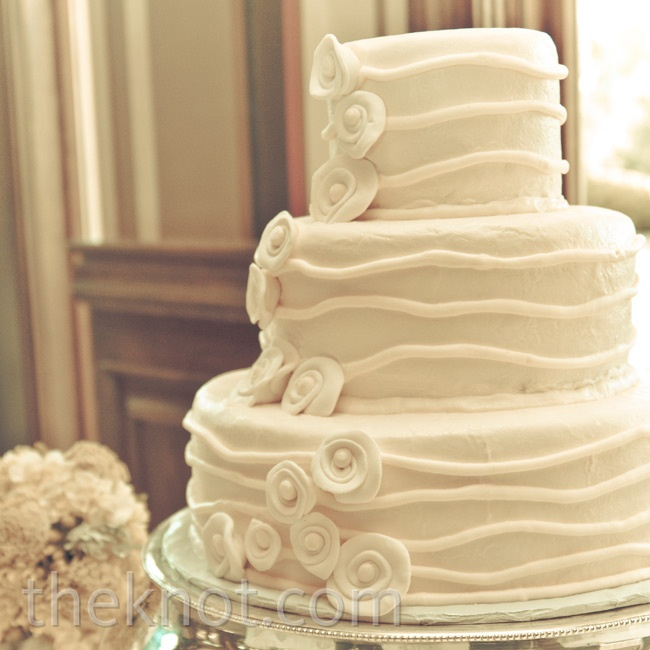 The all-white cake was embellished with simple fondant striping and mod rosettes.