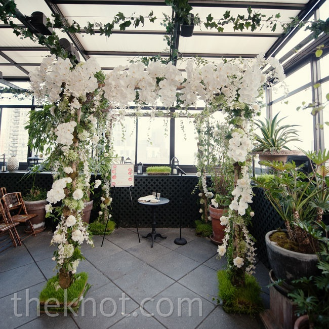 "The couple said their ""I dos"" beneath a huppah covered in white orchids and greenery."