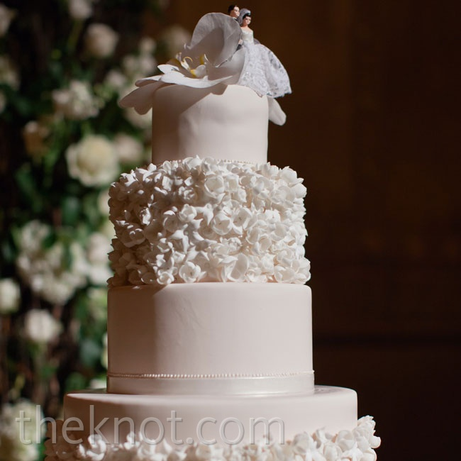 Sugar flowers designed to mimic Tracy's bouquet covered the bottom and middle tiers of the blush fondant confection.