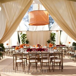 Sparsely draped cream fabric inside a clear tent let sunlight stream into the outdoor reception space.