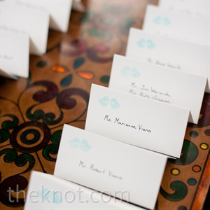 Alyssa&#39;s mother-in-law stamped the tented escort cards with the couple&#39;s lovebird motif.