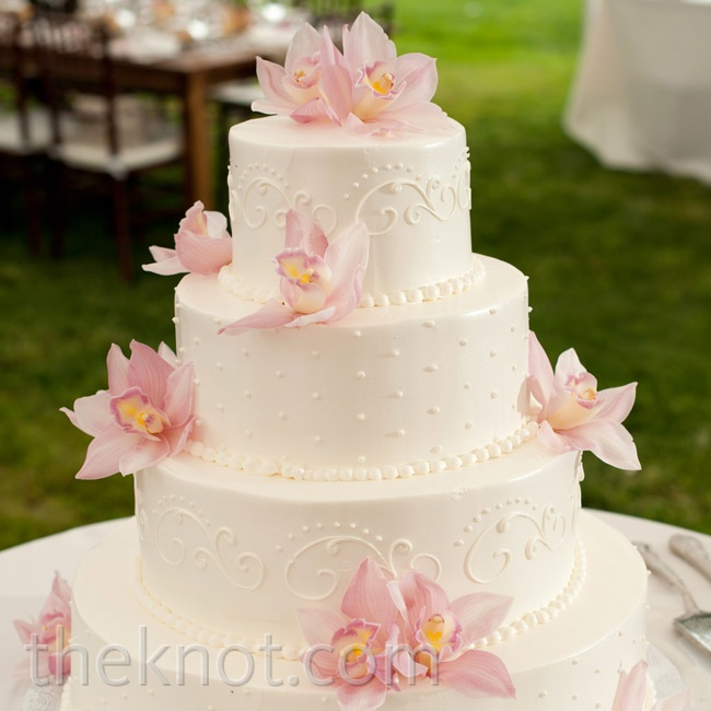 Fresh pale-pink blooms and an elegant scroll design decorated the white cake.