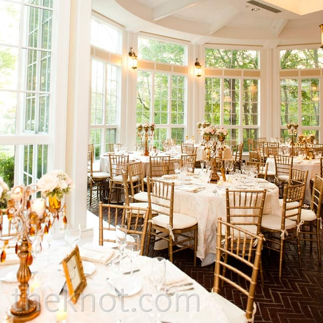 The window-lined room of the couple's wedding venue let in plenty of natural light--complementing the white table linens and gold chairs perfectly.