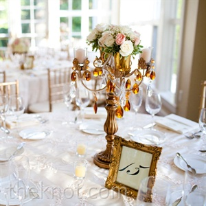 Elegant floral-topped candelabras and gold frames served as focal points on some reception tables.