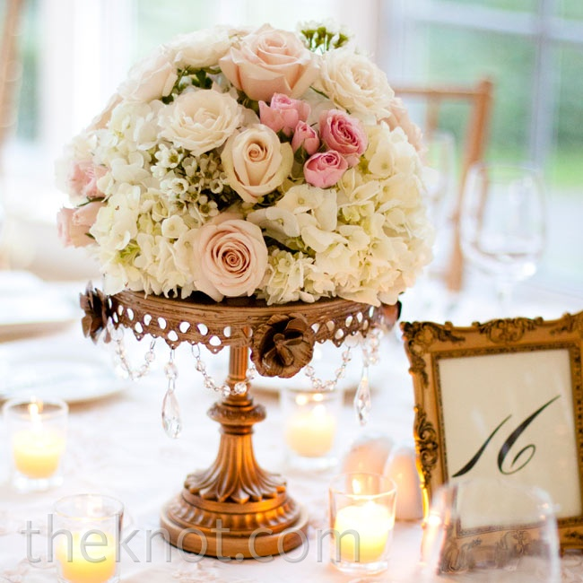 A mixture of cream and blush roses, ranunculus, and hydrangeas rested atop bronze cake stands.