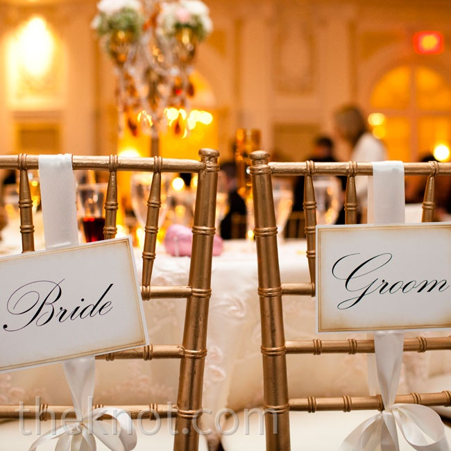 """Bride"" and ""Groom"" signs hung from the couple's seats at the reception."