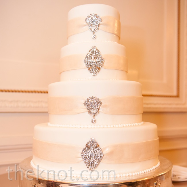 The glam cake was wrapped with a champagne-fondant ribbon and finished with real brooches.