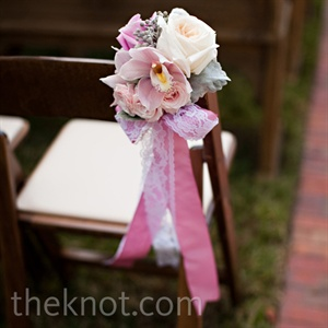 Lace was incorporated into nearly every detail, including the ribbons that accented the ceremony aisle arrangements.