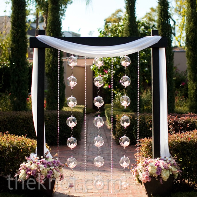 Orchid-filled glass balls hung from a wooden arbor to give the outdoor garden a modern feel.