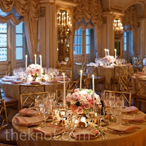 Tapered candles surrounded the low centerpieces of roses and hydrangeas in brass urns for a warm ambience.