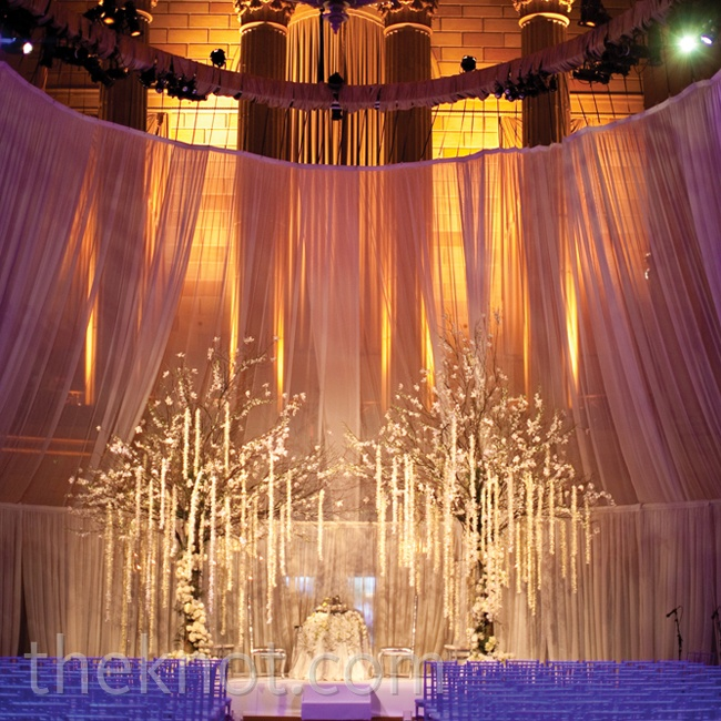 A cool, lavender tint and warm candlelight uplit the soft-ivory draping, making the expansive space feel more intimate.