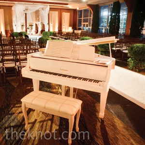 Two white baby grand pianos welcomed guests into the ceremony space, which also included a white-carpet aisle, green shrubbery and a white-silk huppah.