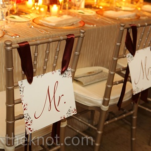 """Mr."" and ""Mrs."" signs hung from red ribbon at the newlyweds' seats."