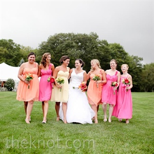 The bridesmaids wore matching one-shoulder chiffon dresses in pink, peach, and yellow.