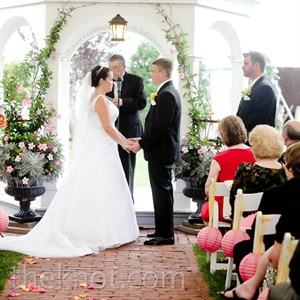 Stefanie and Mark exchanged vows in front of a white gazebo decorated with flowers.