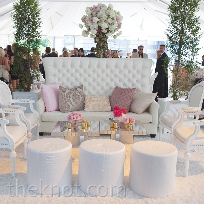 Small gold bud vases holding pink open roses were scattered across the all-white lounge area to incorporate a few touches of the wedding colors.