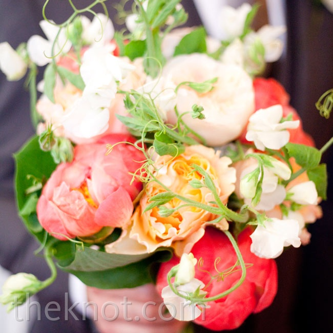 Kelly carried a bright bouquet of coral and peach peonies mixed with various greens.