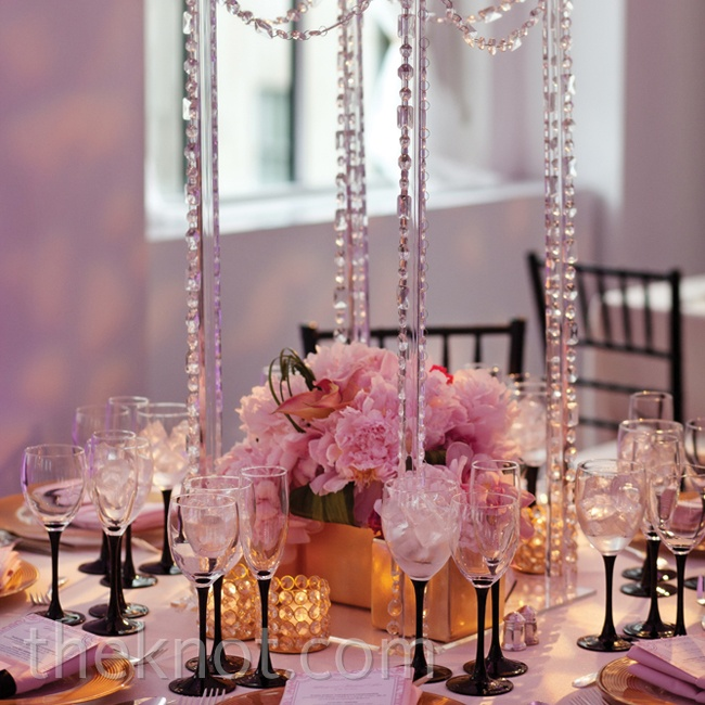 Setting candles atop Lucite stands created the illusion that they were floating throughout the reception space, and low arrangements beneath kept the tablescape modern.