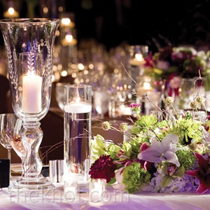 Candles set in mixed glass containers created a warm glow, while low arrangements of eclectic green and plum flowers, like spider mums, lilies, scabiosa pods and dahlias, gave the tables lots of texture.