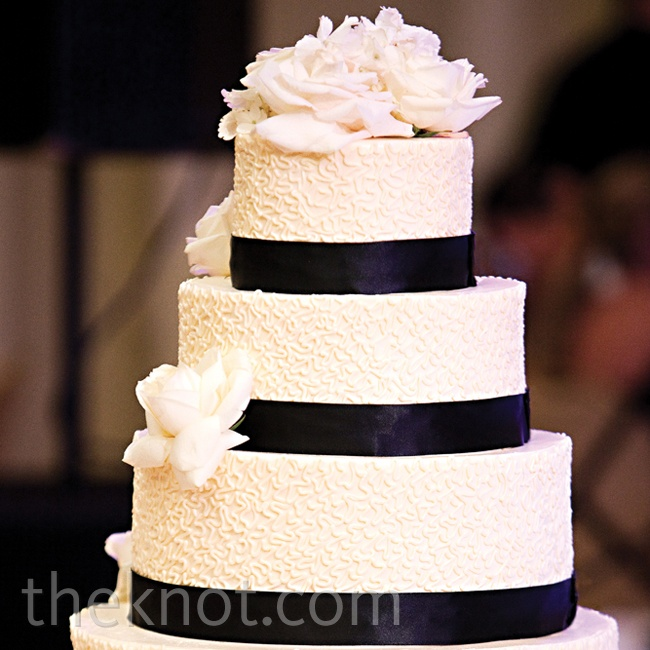 Floral fondant cutouts and black-satin bands adorned the cake, giving it a traditional, yet grand look.