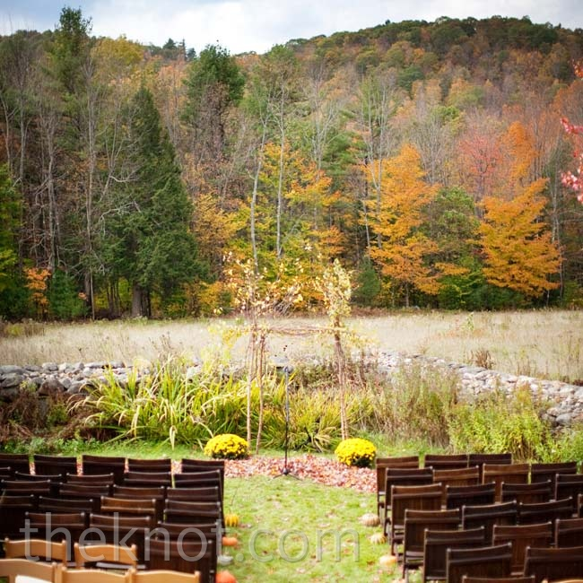 Pumpkins and gourds lined the grassy aisle, while a branch arbor was the centerpiece.
