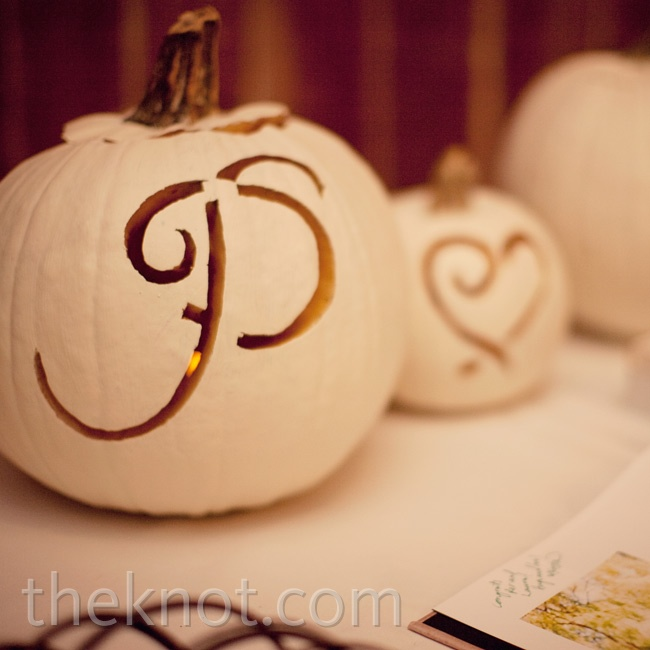 White-painted pumpkins carved with the couple's initials decorated he guest book table.