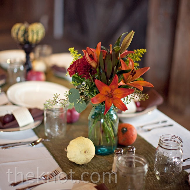 Mason jars filled with vibrant orange flowers topped moss-green table runners.